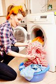 picture of dirty-laundry  - Portrait of attractive housewife putting the laundry into the washing machine - JPG