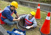 stock photo of sewage  - two sewerage workers in the manhole - JPG