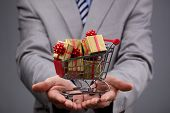 foto of gift wrapped  - Businessman with shopping cart full of gift boxes concept for gift shopping - JPG