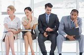 stock photo of sitting a bench  - Four business people waiting for job interview in a bright office - JPG