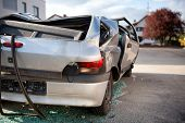 picture of bent over  - Totaled hatchback motor vehicle after a smash viewed from behind showing a flattened roof and shattered windows as though it rolled over with glass shards underneath and bent and buckled bodywork - JPG