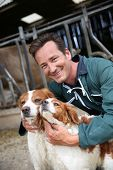 foto of cattle dog  - Breeder petting dogs outside the barn - JPG