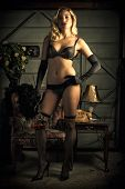 image of fishnet  - A young attractive and sexy blond woman stands holding roses wearing black bra and panties elbow gloves fishnets and heels - JPG