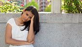 stock photo of suicide  - Closeup portrait dull upset sad young woman in white dress sitting on bench really depressed down about something isolated gray background - JPG