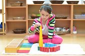 picture of shaky  - Little girl hand building tower made of montessori educational materials - JPG