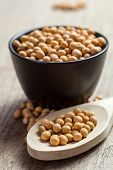 stock photo of soya beans  - Soya beans in a wooden spoon and a black bowl