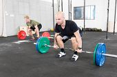 stock photo of jerk  - Two men taking deadlifts or clean and jerk at fitness center - JPG