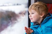 image of passenger train  - Beautiful toddler boy looking out train window outside while it moving - JPG