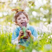stock photo of bunny ears  - Happy little toddler boy eating chocolate and wearing Easter bunny ears sitting in blooming garden on warm sunny day - JPG