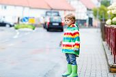 picture of rainy season  - Funny cute kid boy walking in city through rain wearing colorful rain coat and green boots outdoors at rainy day - JPG