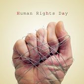 stock photo of torture  - a man hand tied with wire and the text human rights day on a beige background - JPG