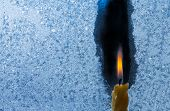 picture of candle flame  - Closeup photo of little candle flame behind frozen window glass - JPG