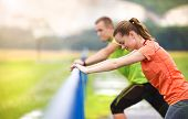 image of rainy weather  - Young couple stretching after the run on asphalt in rainy weather - JPG