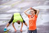 picture of rainy weather  - Young couple stretching after the run on asphalt in rainy weather - JPG