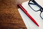 stock photo of ballpoint  - Red ballpoint pen and and a pair of reading glasses lying on pages of blank white paper on a wooden desk with copyspace overhead view - JPG