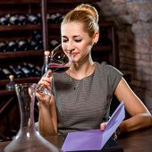 foto of wine cellar  - Young woman tasting wine in the cellar. Wine degustation