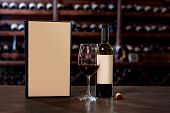 picture of wine cellar  - Wine bottle with glass and menu on the table at the wine cellar