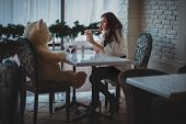 stock photo of pity  - Girl sitting in a restaurant with a bear face to face and sad - JPG