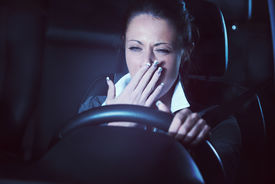 image of unsafe  - Distracted exhausted tired woman driving a car late at night - JPG