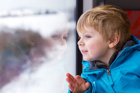 stock photo of passenger train  - Beautiful toddler boy looking out train window outside while it moving - JPG