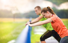 stock photo of rainy weather  - Young couple stretching after the run on asphalt in rainy weather - JPG