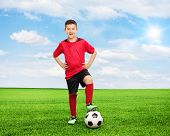 stock photo of youngster  - Full length portrait of a cheerful youngster standing over a football on a green field on a sunny summer day - JPG