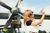 image of propeller plane  - beautiful woman holding paper plane against real plane - JPG