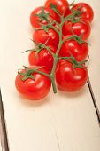 foto of cluster  - fresh cherry tomatoes on a cluster over rustic wood table - JPG