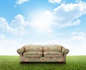 stock photo of green-blue  - A green and pink floral sofa outside on a perfect flat green lawn against a blue sky with white clouds - JPG