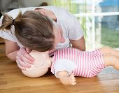 foto of check  - Woman performing CPR on baby training doll checking for signs of breathing - JPG