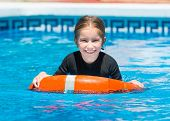 picture of lifeline  - happy little girl swims in a wetsuit with a lifeline in the pool in  summer - JPG