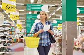 stock photo of supermarket  - Woman housewife with list shopping in supermarket - JPG