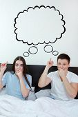 stock photo of bubble sheet  - Handsome man and pretty surprised woman in bedroom showing up at thinking speech bubble comic cloud or empty copyspace - JPG