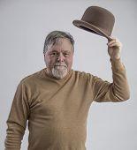 picture of older men  - Older man in brown sweater doffing brown derby and smiling - JPG