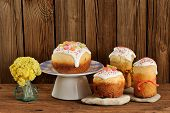 foto of easter candy  - Kulich Russian easter sweet breads decorated with icing and candied fruits with yellow flowers on wooden background with space - JPG