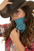 stock photo of cowgirls  - a cowgirl with a bandana over her face holding on to her hat - JPG
