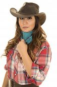 stock photo of cowgirls  - A cowgirl with a serious expression on her face touching her bandana - JPG