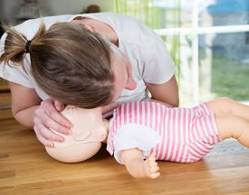 picture of baby doll  - Woman performing CPR on baby training doll checking for signs of breathing - JPG