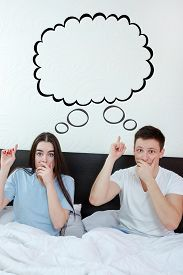 picture of bubble sheet  - Handsome man and pretty surprised woman in bedroom showing up at thinking speech bubble comic cloud or empty copyspace - JPG