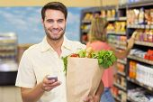 pic of supermarket  - Portrait of smiling handsome man buying food products and using his smartphone at supermarket - JPG