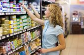 stock photo of supermarket  - Pretty blonde woman taking a products in shelves in supermarket - JPG