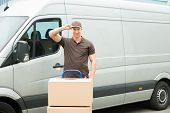 foto of moving van  - Happy Delivery Man With Cardboard Boxes In Front Van - JPG