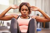 picture of crunch  - Young woman doing crunches in a gym - JPG