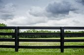 stock photo of pastures  - Black painted fence along a horse pasture right before a summer storm - JPG