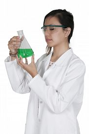 foto of beaker  - Beautiful woman scientist investigating a glass beaker - JPG