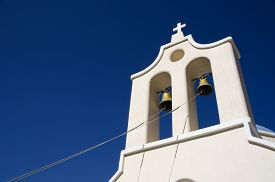 stock photo of blue-bell  - Ropes attached to the bells of a bell tower in front of the blue sky of a church in Santorini Greece - JPG