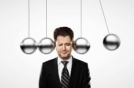 picture of pendulum  - businessman thinking and head metal pendulum - JPG