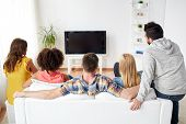 friendship, people and entertainment concept - happy friends watching tv at home poster