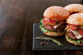 A Delicious And Juicy Burger Home In A Rustic Style With A Big Chop Of Beef poster