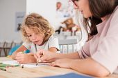 Close-up Of A Child With An Autism Spectrum Disorder And The Therapist By A Table Drawing With Crayo poster